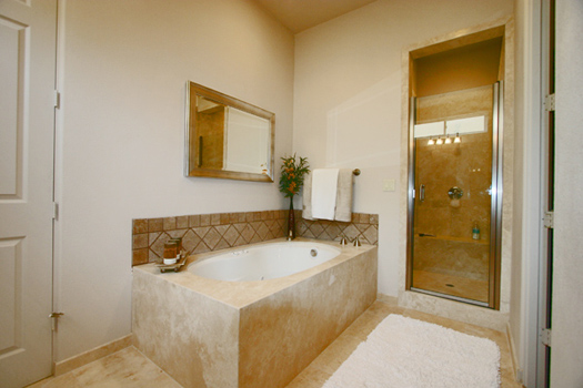Master bathroom with jetted spa tub and separate shower all finished in slab travertine marble